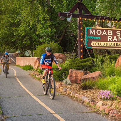 Two male bicyclists on a bike path riding past the rectangular Moab Springs Ranch sign.