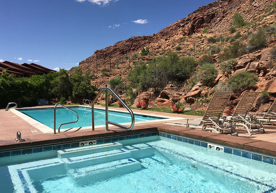 A 42 foot rectangular outdoor swimming pool sits amongst beige chaise lounge pool chairs, green vegetation and the natural brown cliffs of Moab Springs Ranch.