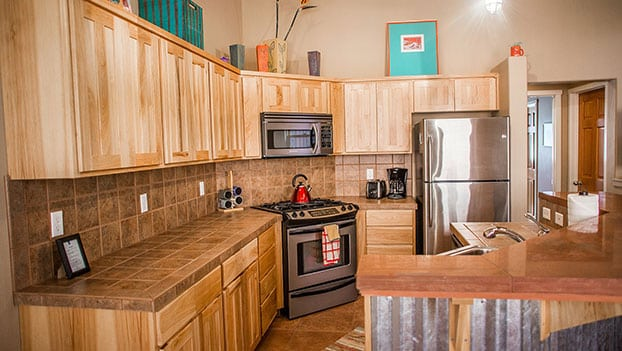 Small photo of a kitchen unit with lots of natural beige wood cabinets and storage, stainless steel appliances and breakfast counter at the Moab Springs Ranch property.