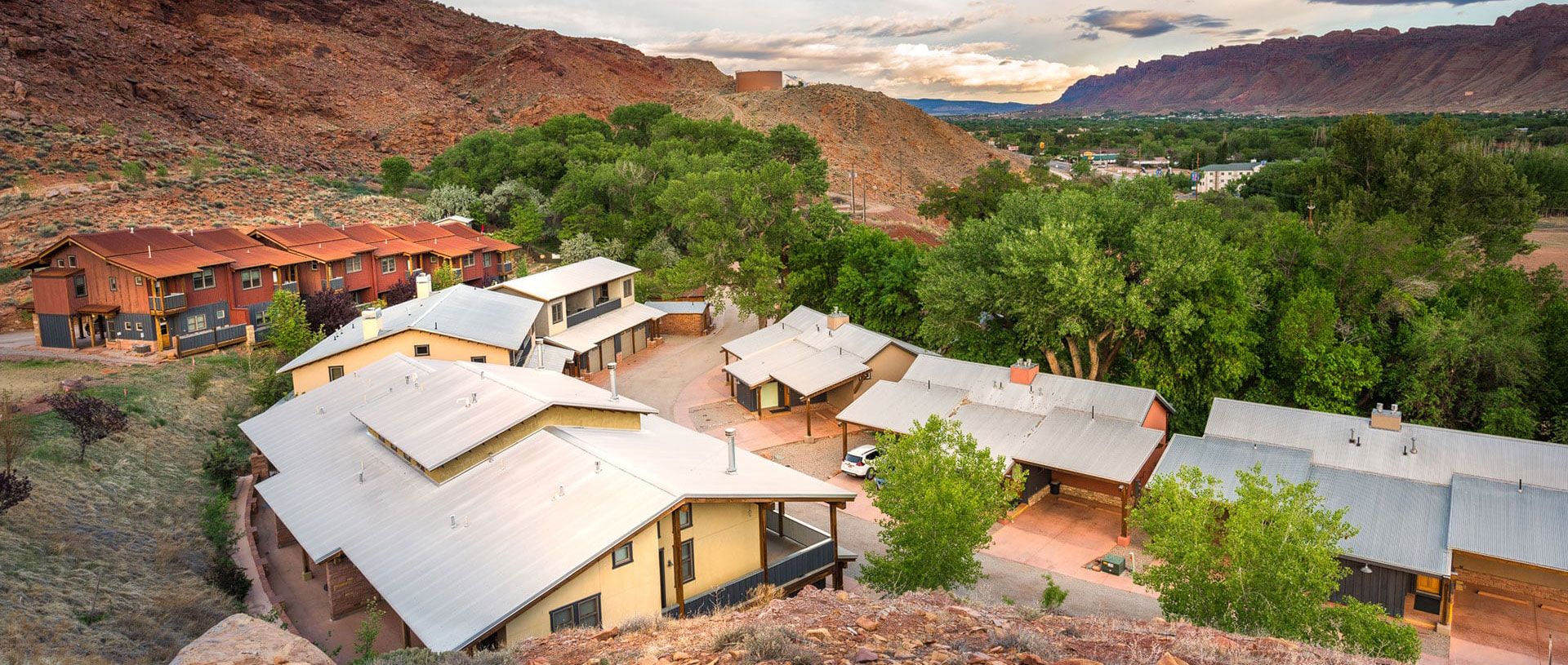 Aerial view of rows of the triangular roofs of townhouse units on Moab Springs Ranch with tall green trees and grasslands, and a rural road leading into the property.
