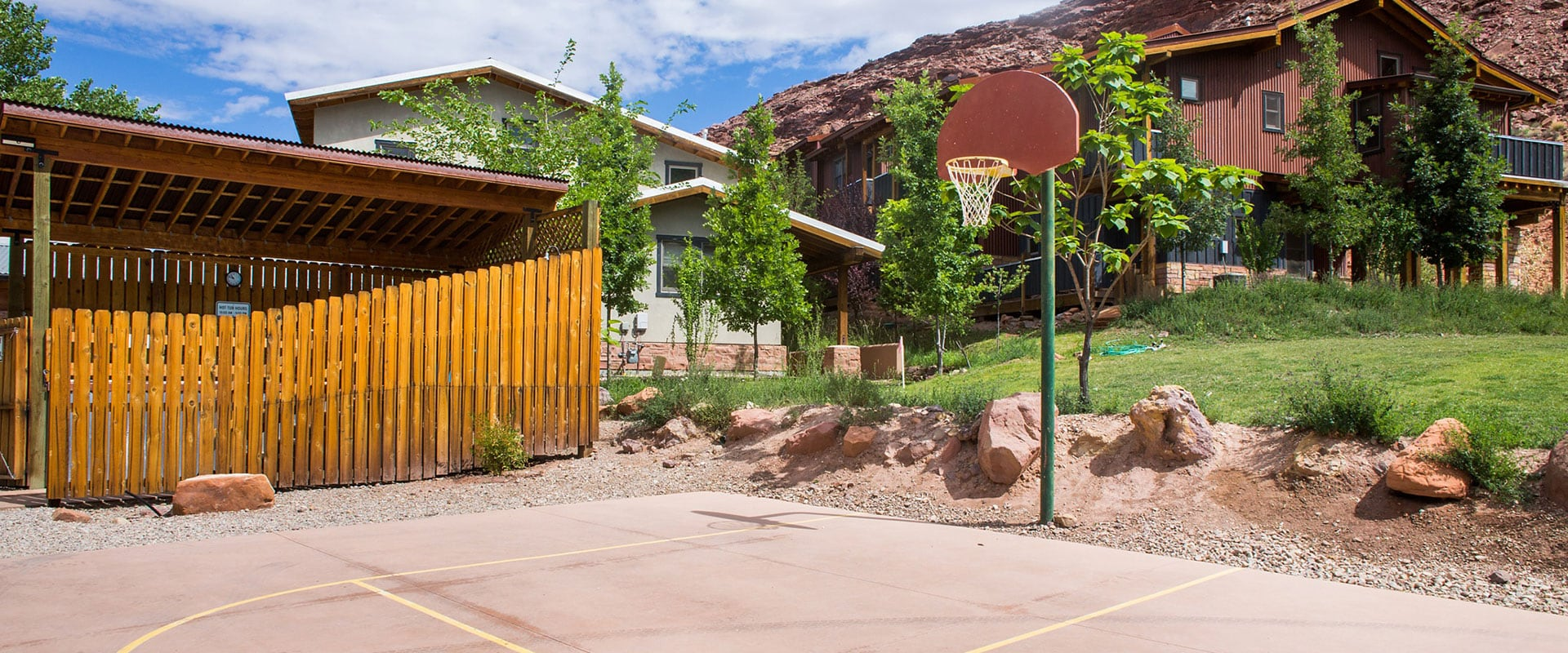The recreation area of Moab Springs Ranch features a basketball court with in-ground pole and hoop and the whirlpool area enclosed by wood slat fences and covered by a slanted wood roof.