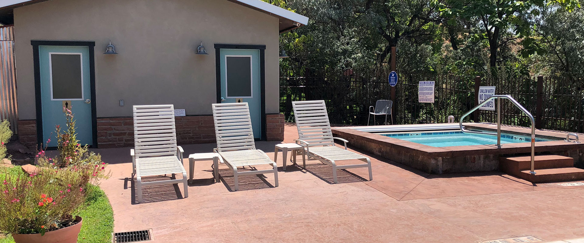 Four sets of black wrought iron tables and chairs are placed over red and white stone pavement at an outdoor seating area for guests of Moab Springs Ranch.