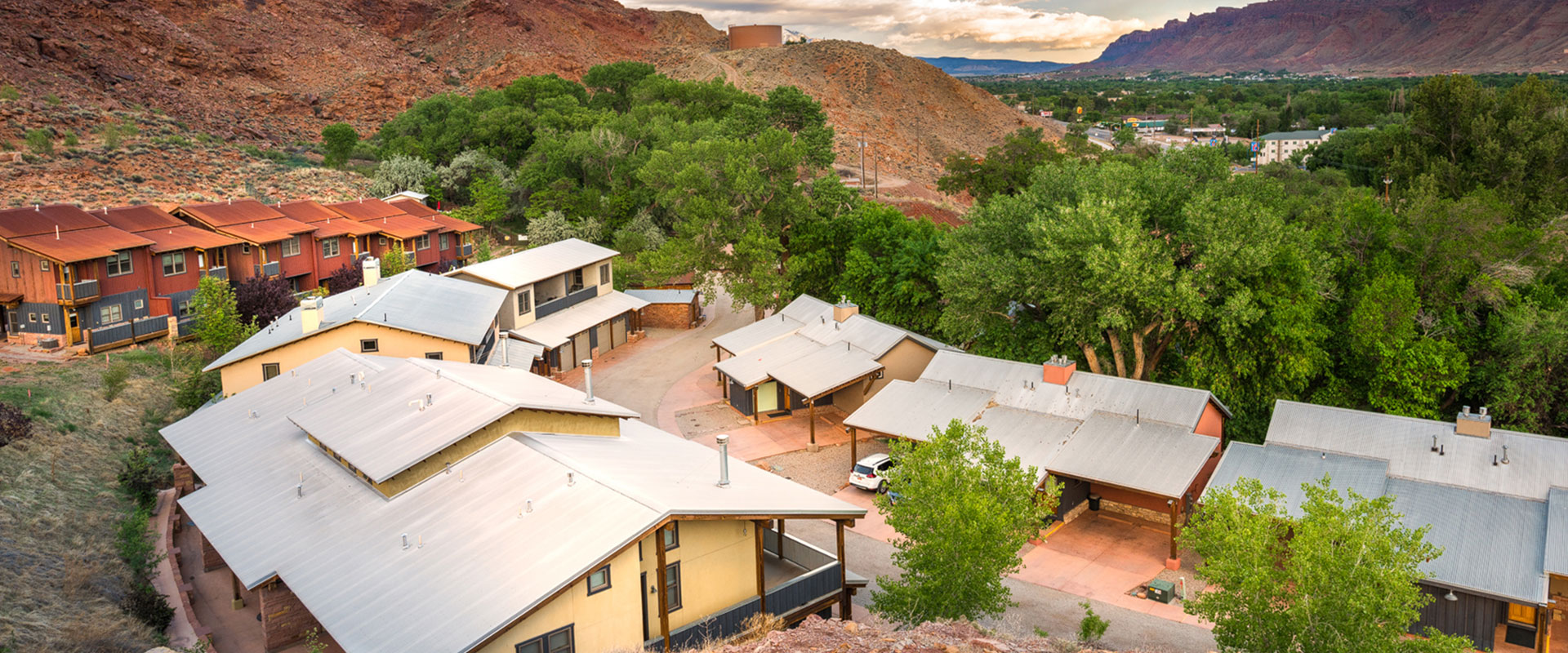 A winding serpentine man-made stream lies alongside a parallel stone paved path amidst green grass space in the public park grounds at Moab Springs Ranch.