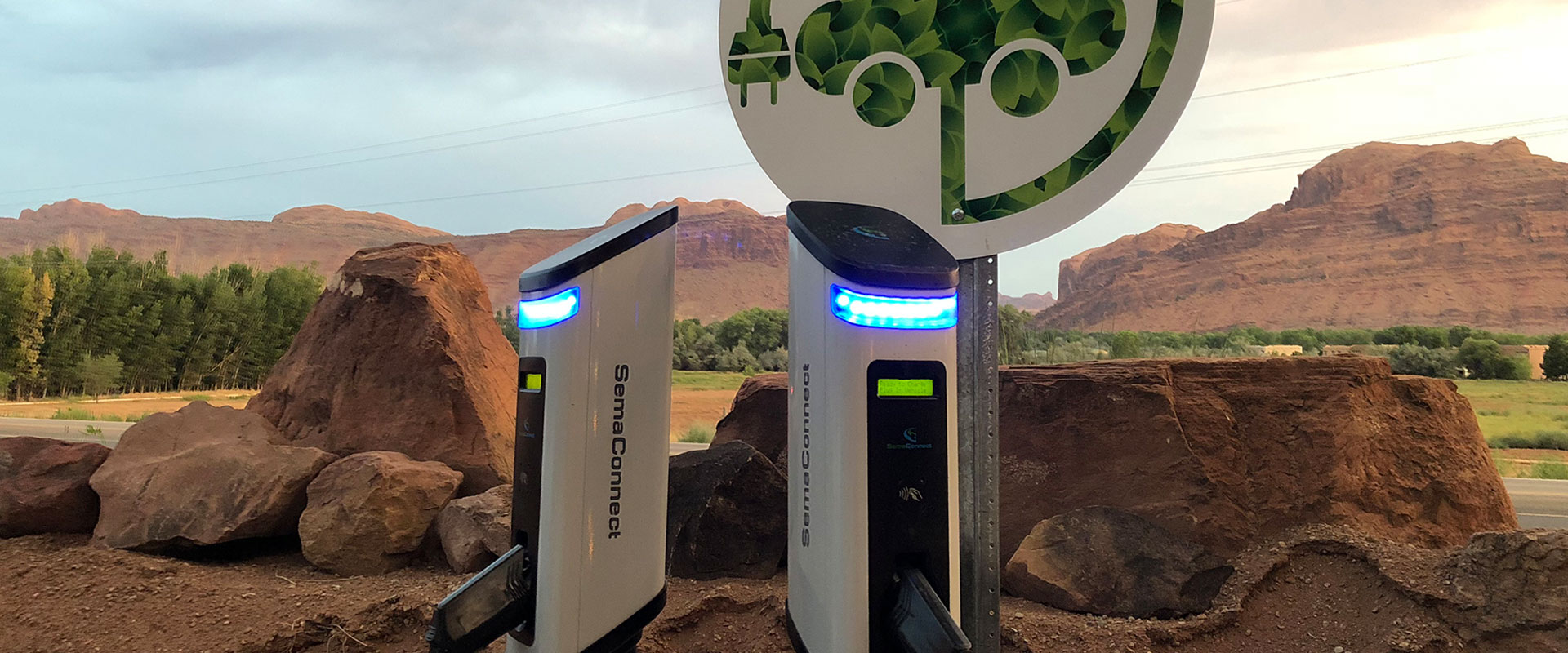 Two freshwater streams run across the vibrant green parkspace with tall trees providing ample shade on the Moab Springs Ranch property.