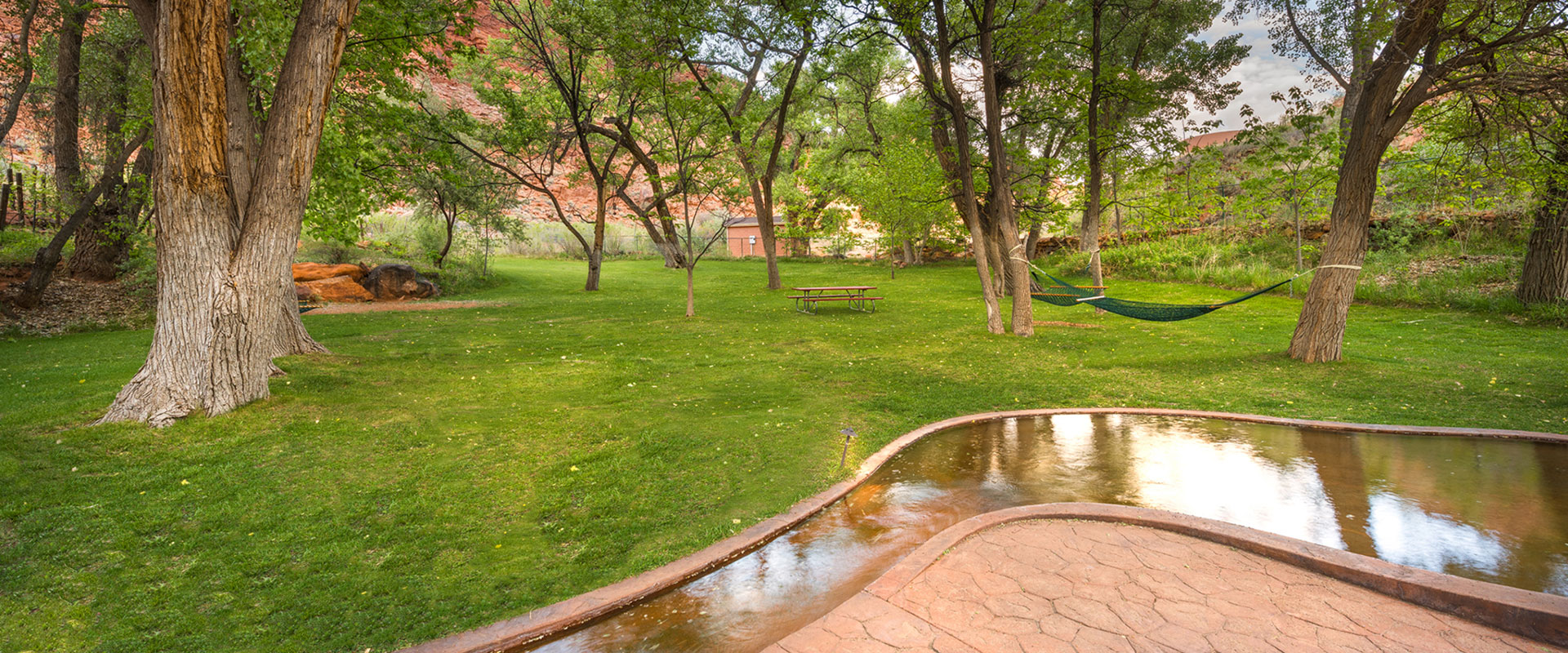 A white loveseat swing set, made of wood slats is set against the background of a ranch style fence and the looming sandstone mountain cliffs of Moab, Utah.