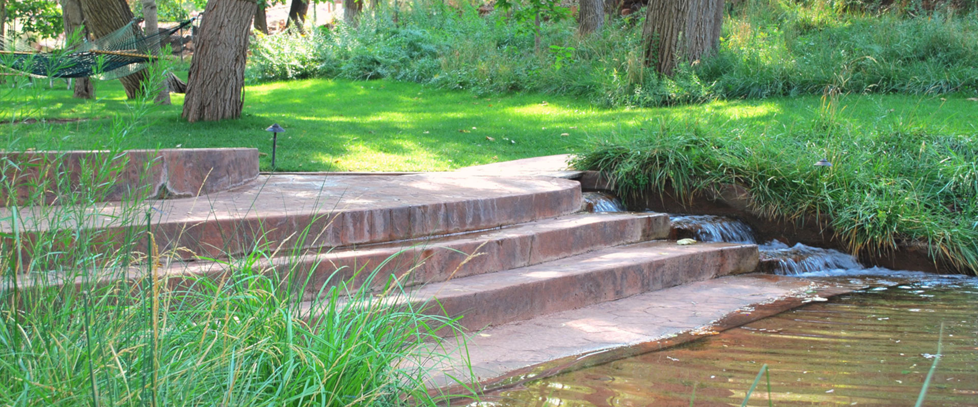 Against the backdrop of the vibrant green grasslands and a picnic table in the private parkspace at Moab Springs Ranch, hammocks are tied to strong and sturdy tree trunks.