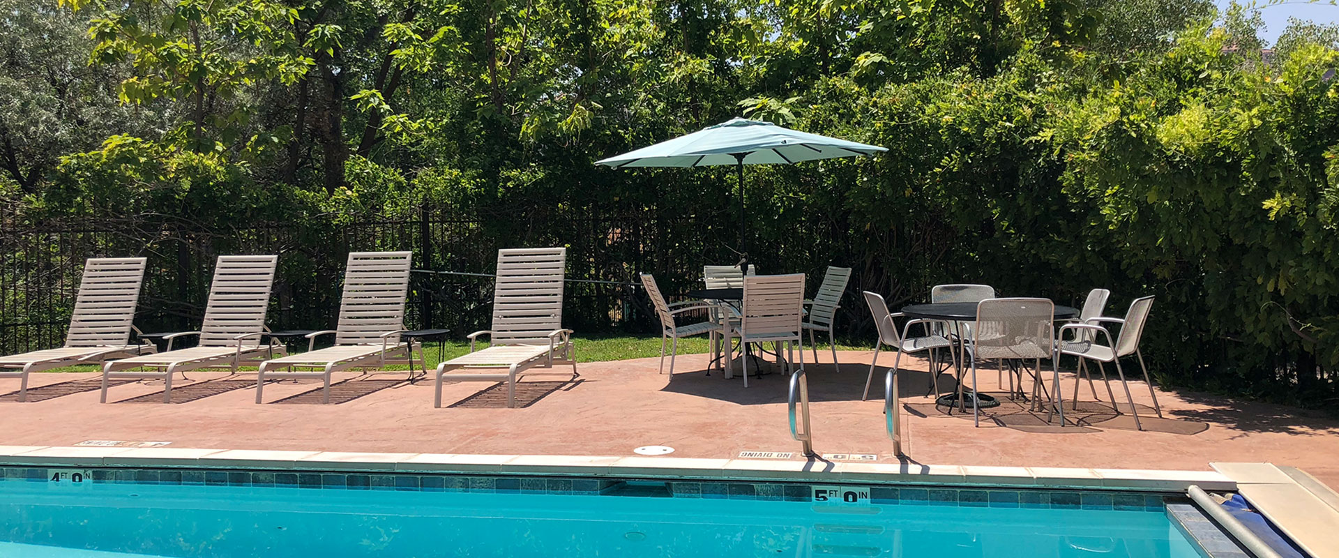 The swimming pool area at Moab Springs Ranch is surrounded by black steel rod fencing with multitudes of purple wisteria flowers lazily dangling over.