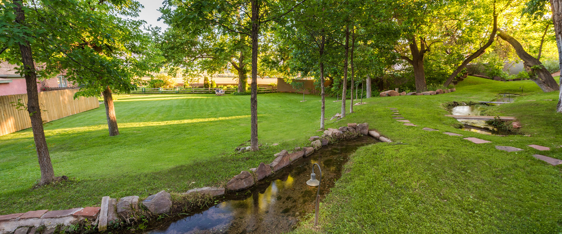 An older male guest, wearing a straw hat, is leaning against a newly painted bright turquoise pick up truck at Moab Springs Ranch in Utah.