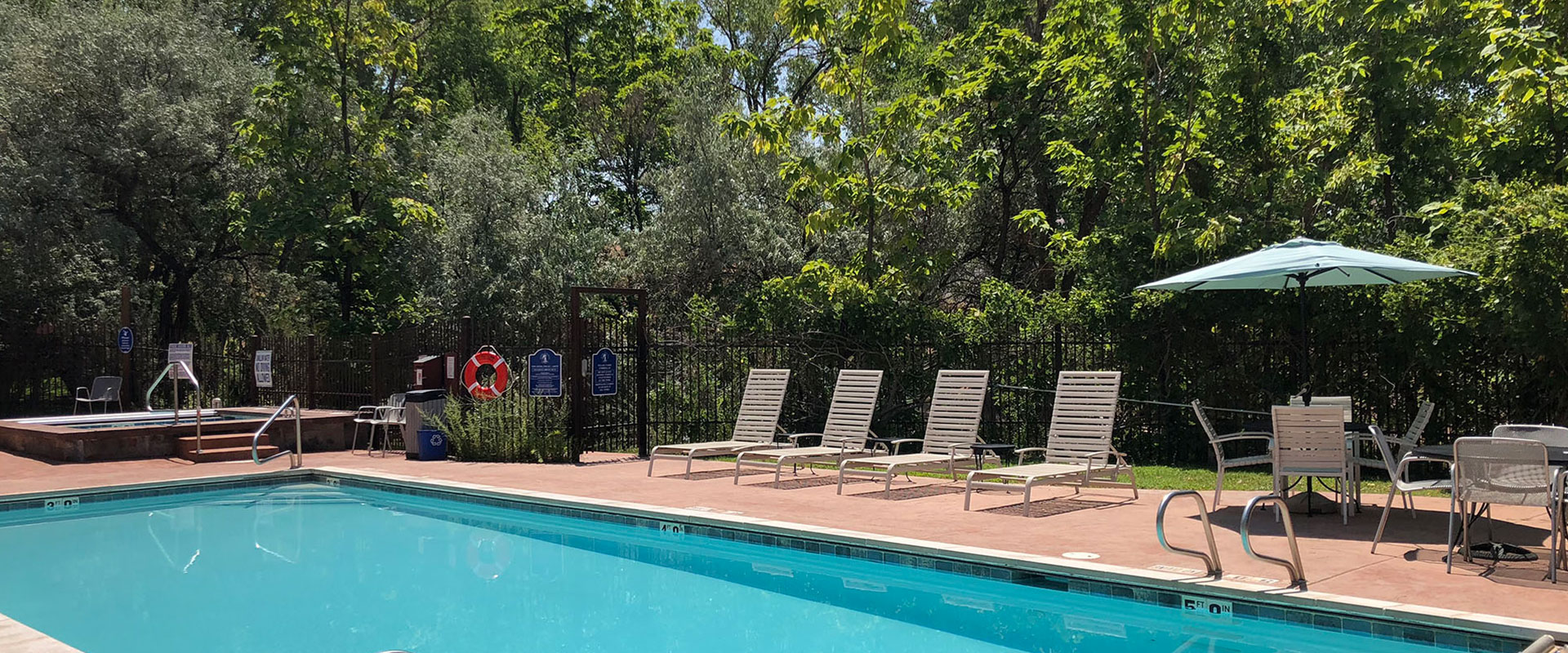A blonde female child in a bathing suit twirling a hula hoop, plays in the man-made stream against the natural backdrop of green grass and trees at Moab Springs Ranch.