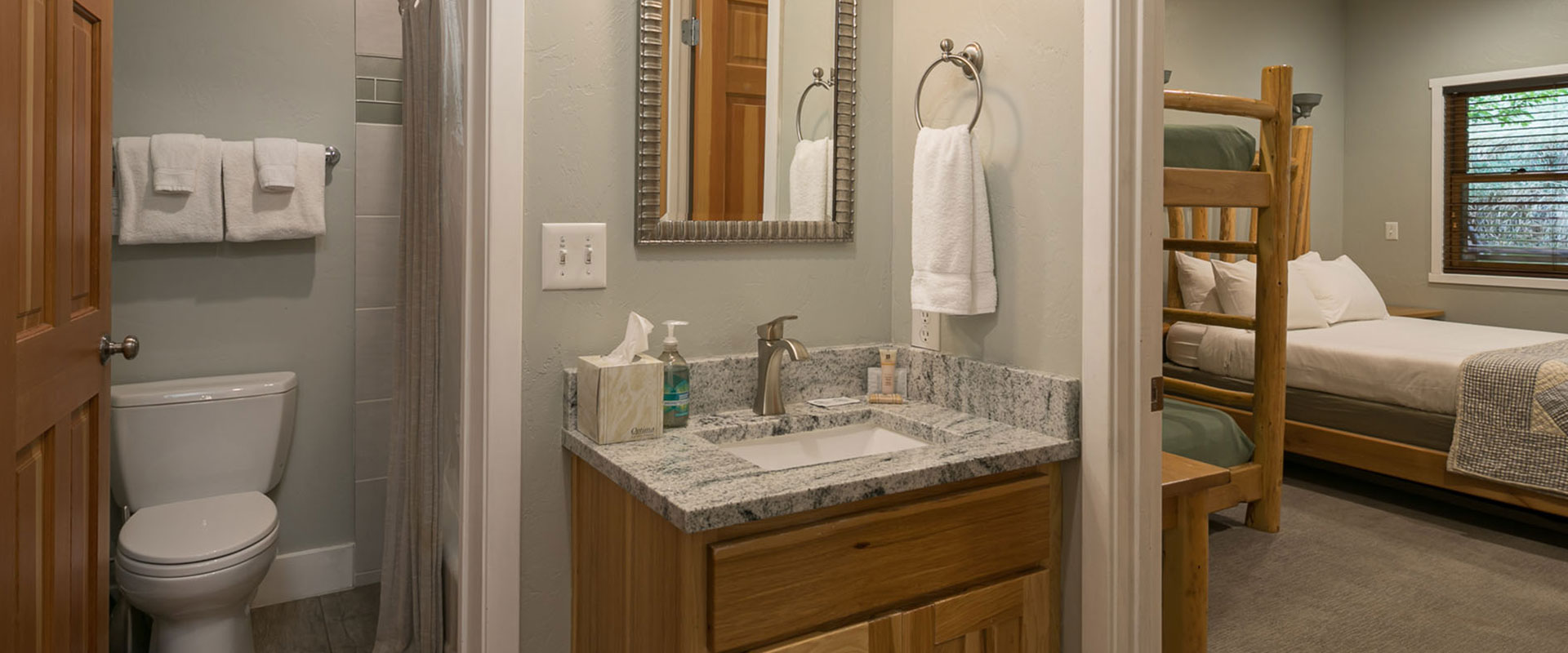 In the daylight, a white ghostly silohuette of a round moon appears against the blue sky and the red brown craggy sandstone cliffs of Moab, Utah.