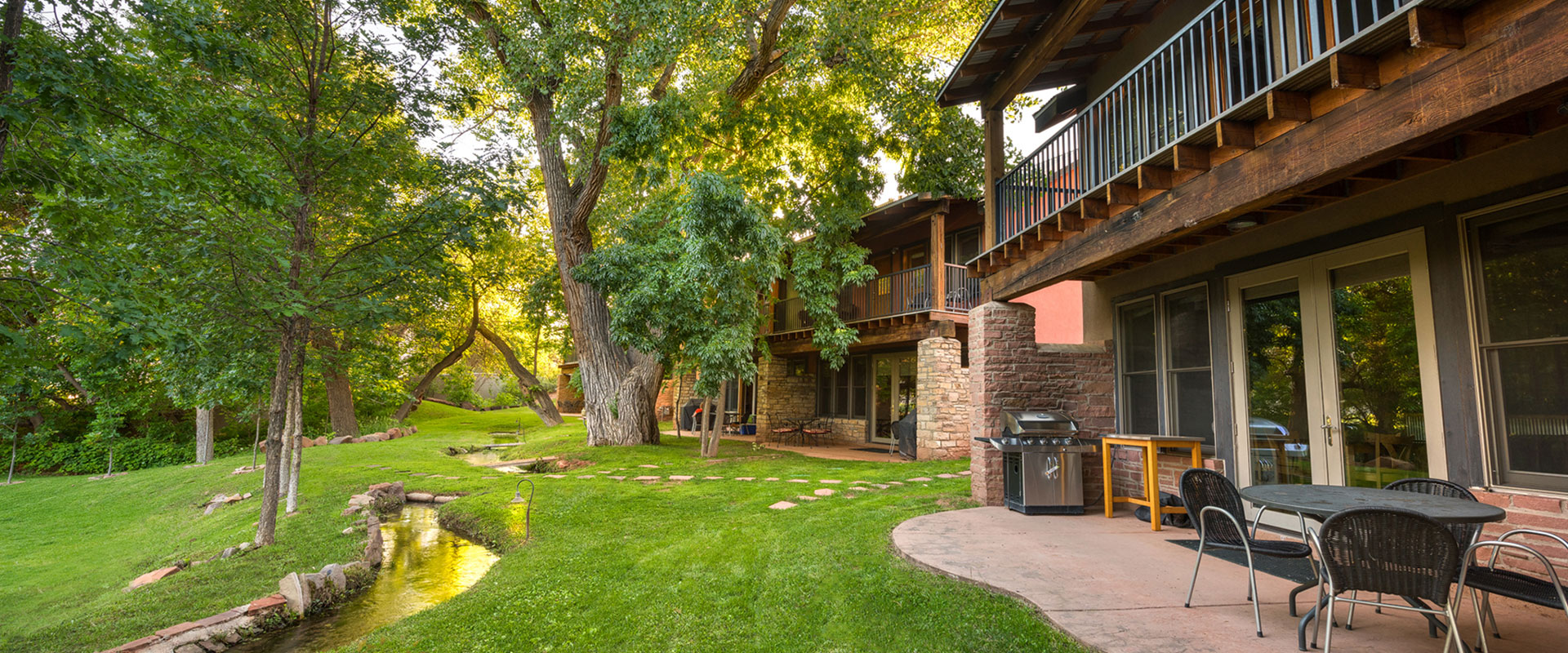 A large aerial view over the sandstone cliffs, the cottonwood tree tops and the sloping white and brown roofs of bungalows and townhomes at Moab Springs Ranch.