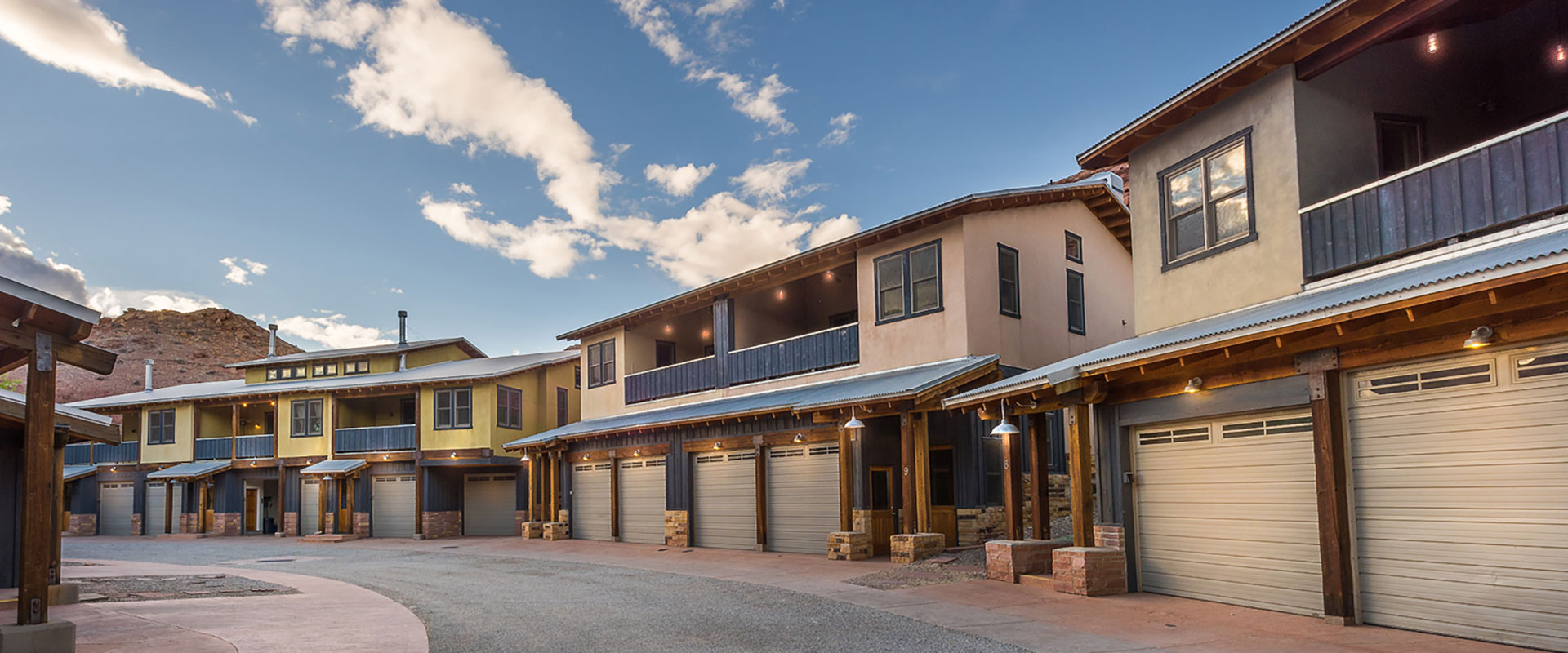A sandstone mountain cliff is covered with a light dusting of snow on a sunny winter day in Moab, Utah.