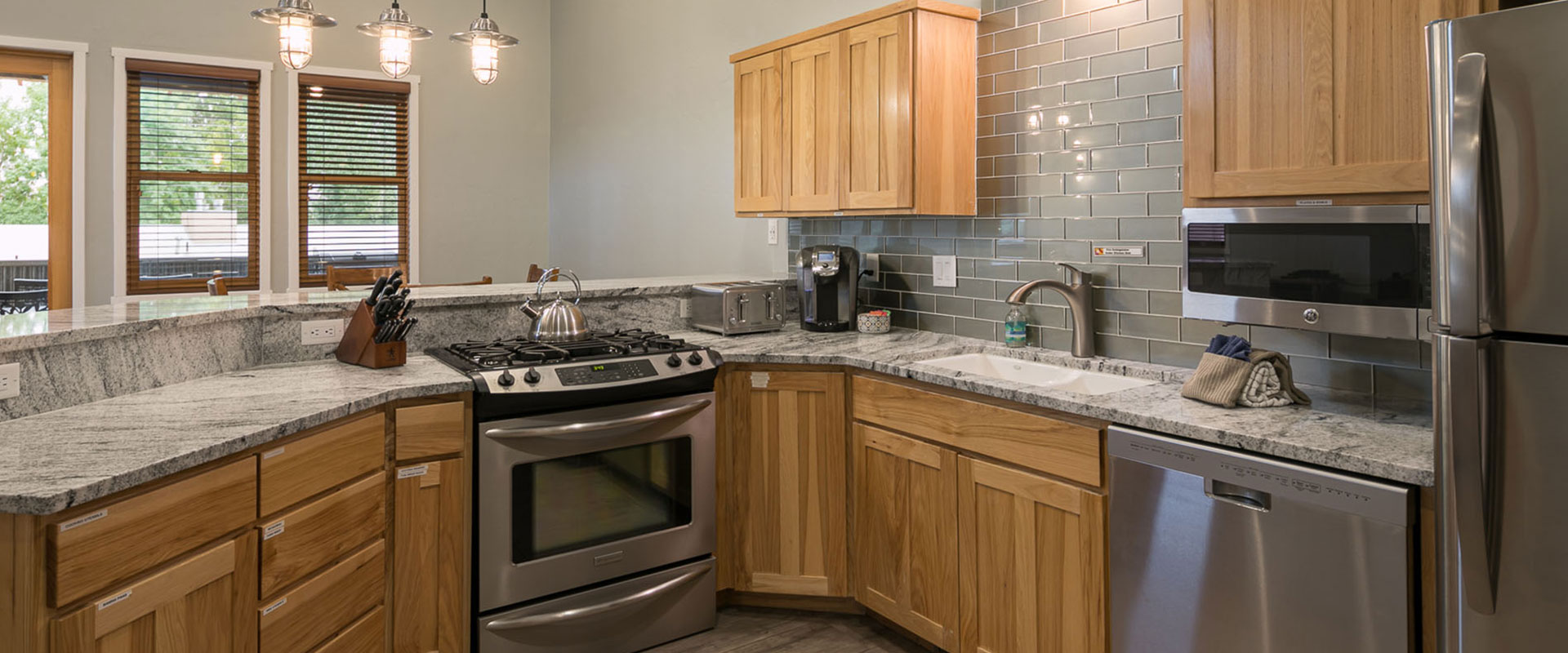 A view of red rocks, verdant trees, vegetation and flat grasslands set against the backdrop of the charcoal grey silhouette of the majestic sandstone cliffs of Moab, Utah.