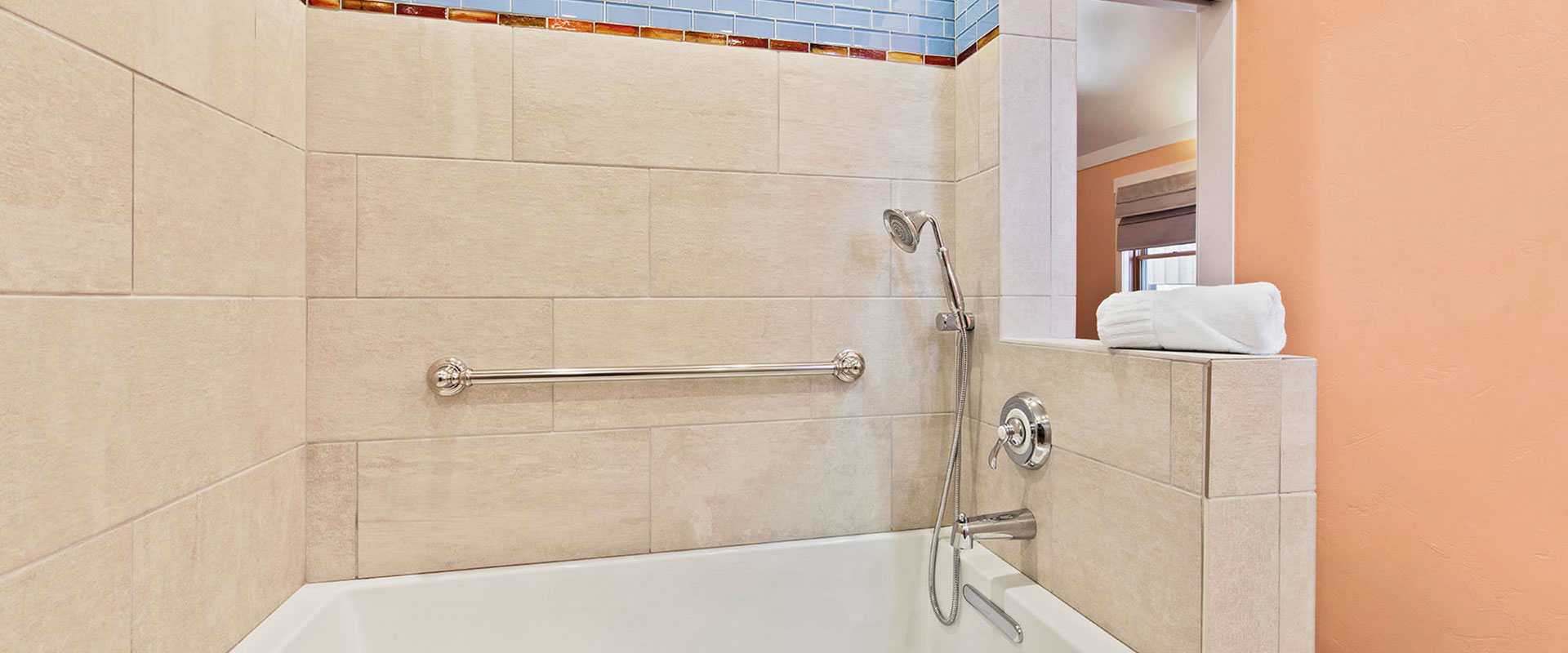 The breakfast nook area of Unit #18 at Moab Springs Ranch is bathed in natural light from two surrounding woodframe windows and the glass inset door leading onto the patio.