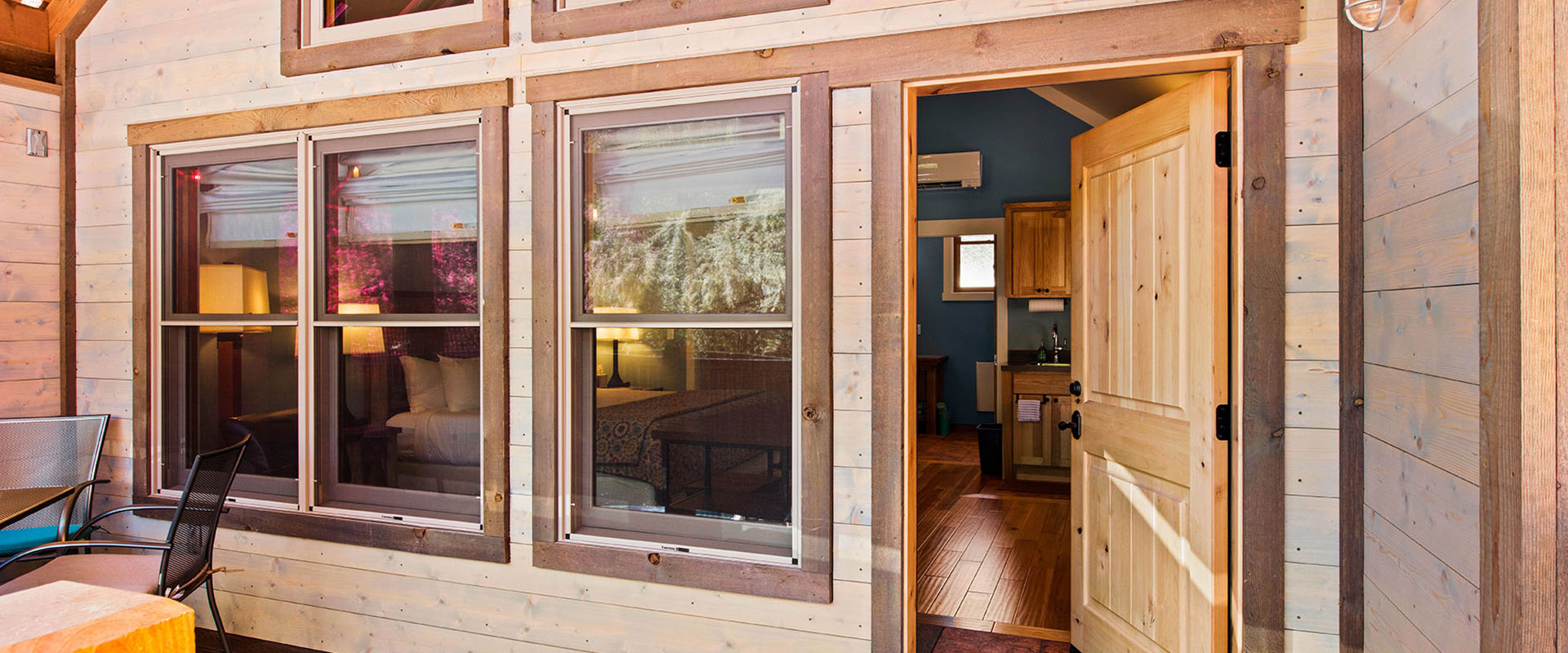 Balcony view from a unit at Moab Springs Ranch overlooking green and plum colored trees, the corrugated roofs of neighboring units and towering sandcliffs in the background.