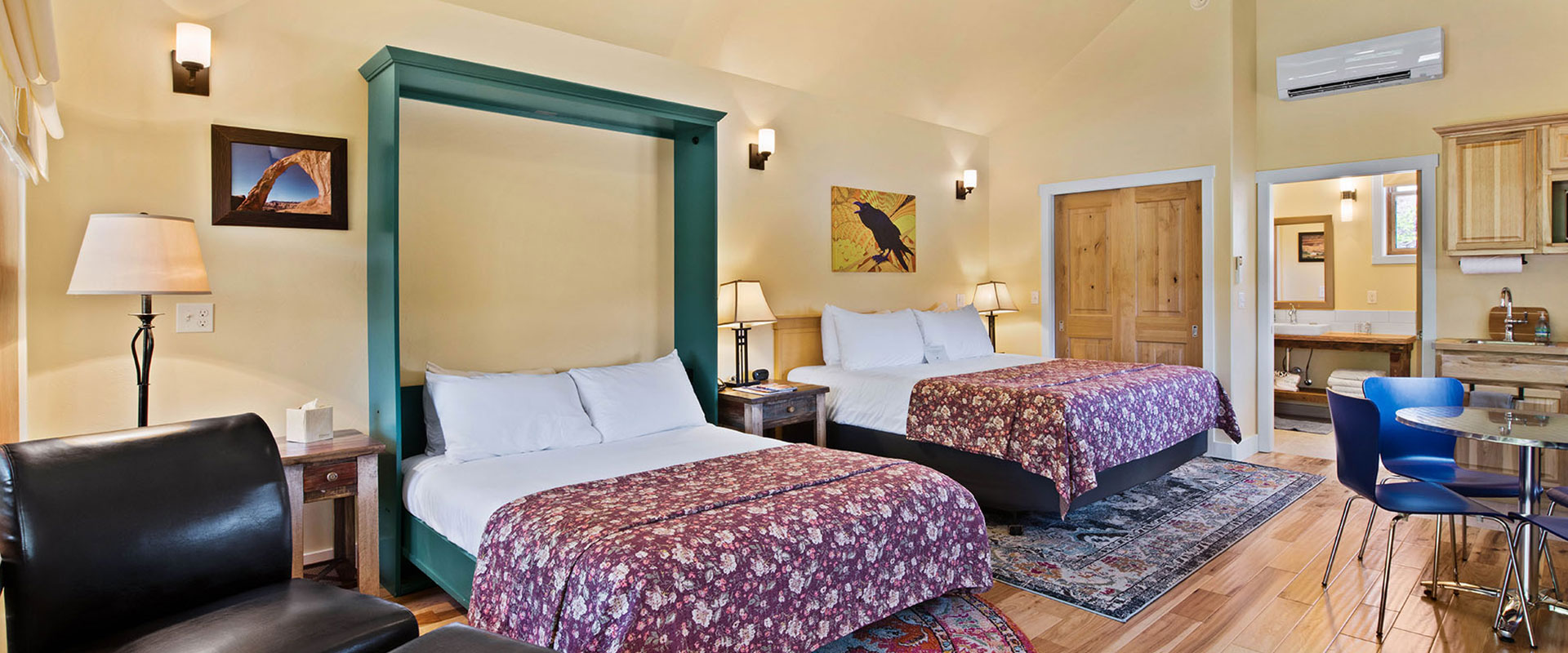 Corrugated metal siding provides an enclosure to the patio of a townhome at Moab Springs Ranch which includes black coated metal patio furniture, wood burning fireplace and barbecue.