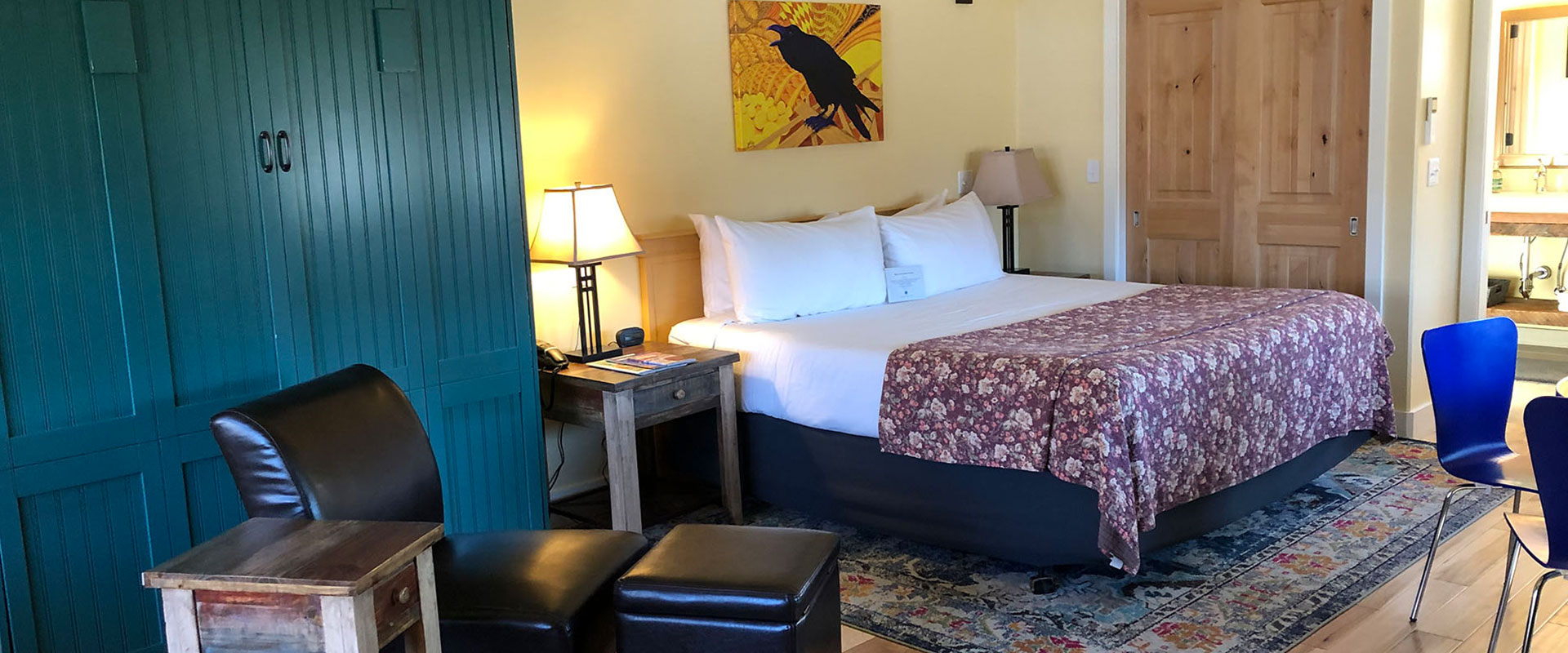 The patio view from Unit #21 at Moab Springs Ranch overlooks triangular rooftops of neighboring townhouse units, green and plum color tree leaves and the black shadow of sandstone cliffs.
