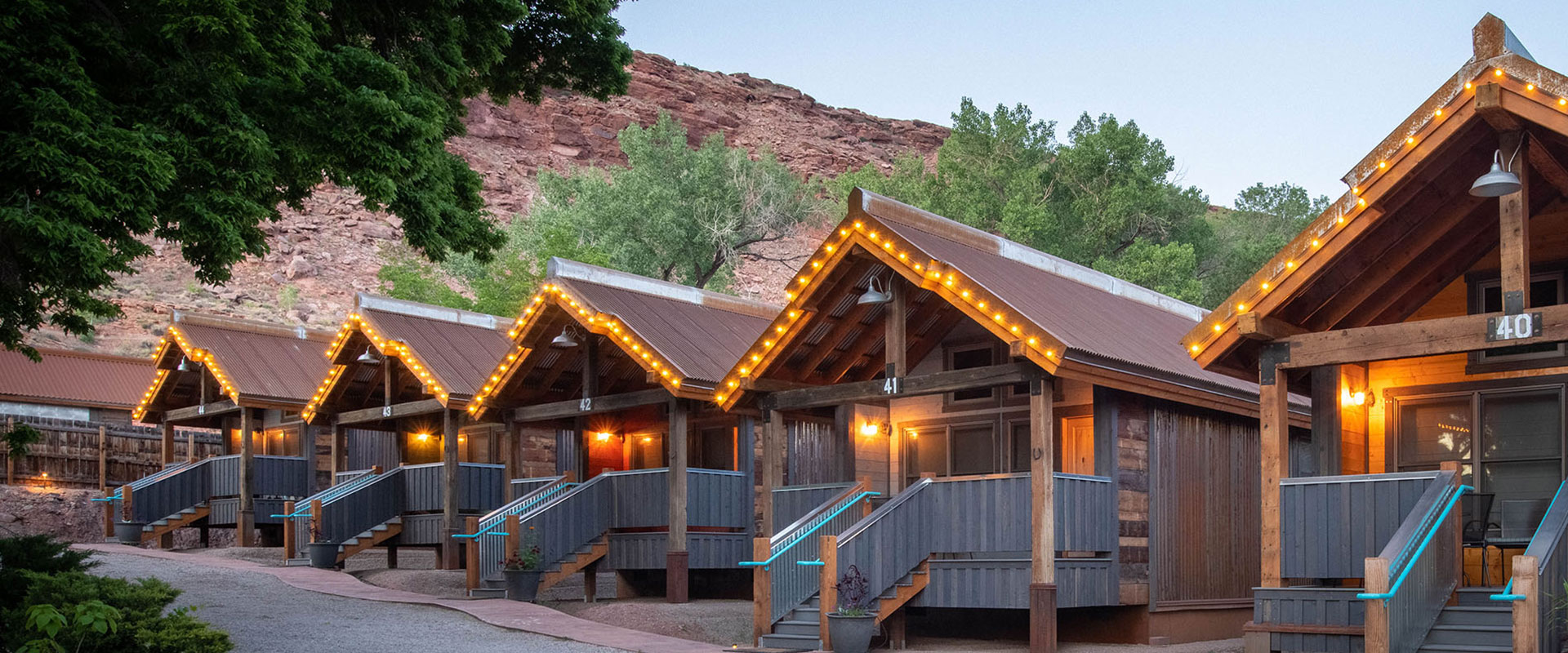A view of two storey townhomes with closed garages and surrounding trees bearing yellow leaves on a cloudy day at Moab Springs Ranch in Utah.