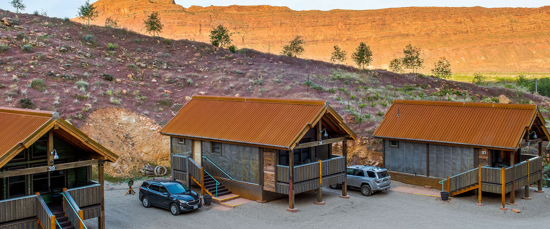 A shallow stream, trees and an outdoor picnic table are found in the yard space of townhouse units at Moab Spring Ranch.