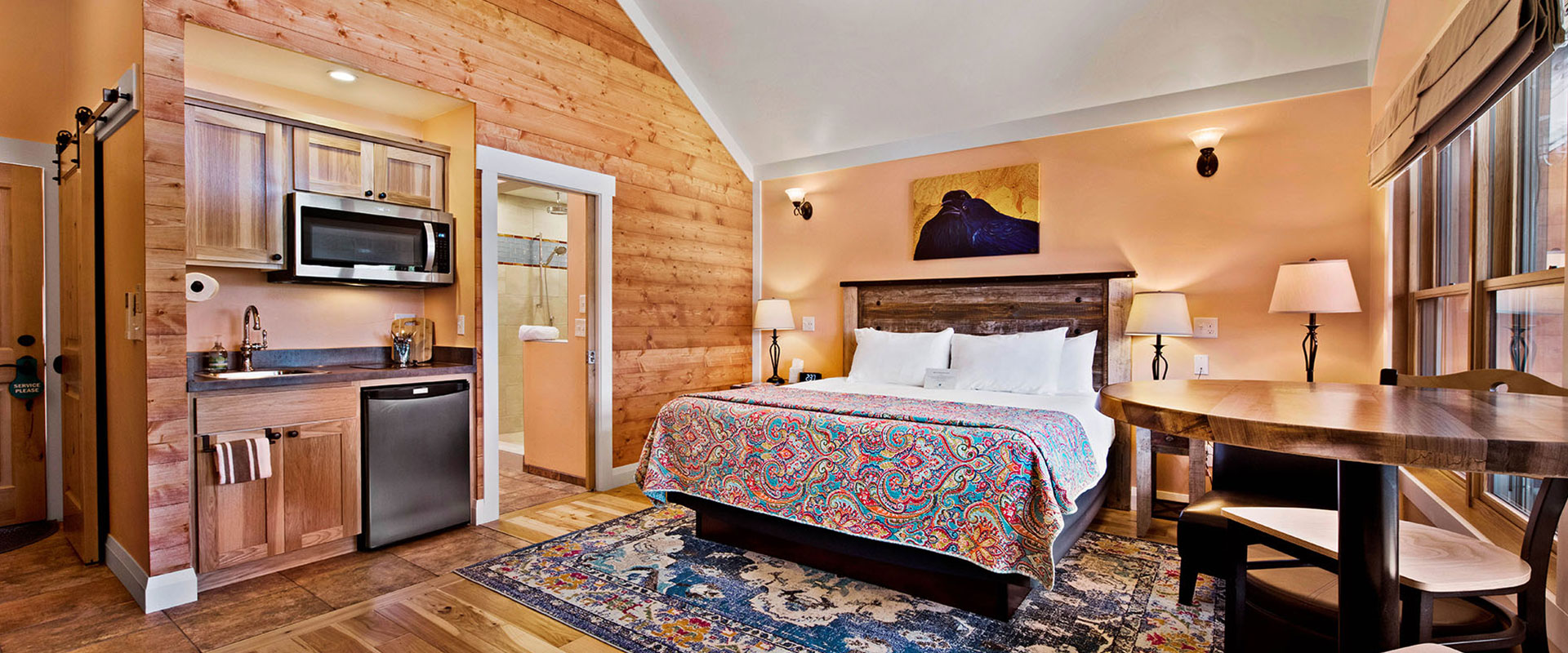 A large view of the kitchen of Unit #18 at Moab Springs Ranch with spacious beige wood cabinets and stainless steel appliances such as stove, refrigerator and microwave.