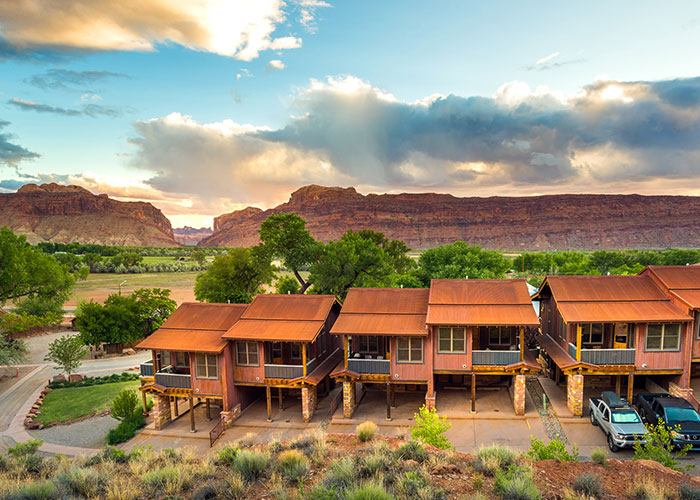 The Moab Springs Ranch road sign sits opposite the grasslands and the imposing sandstone mountains of Moab, Utah underneath a late afternoon sky.