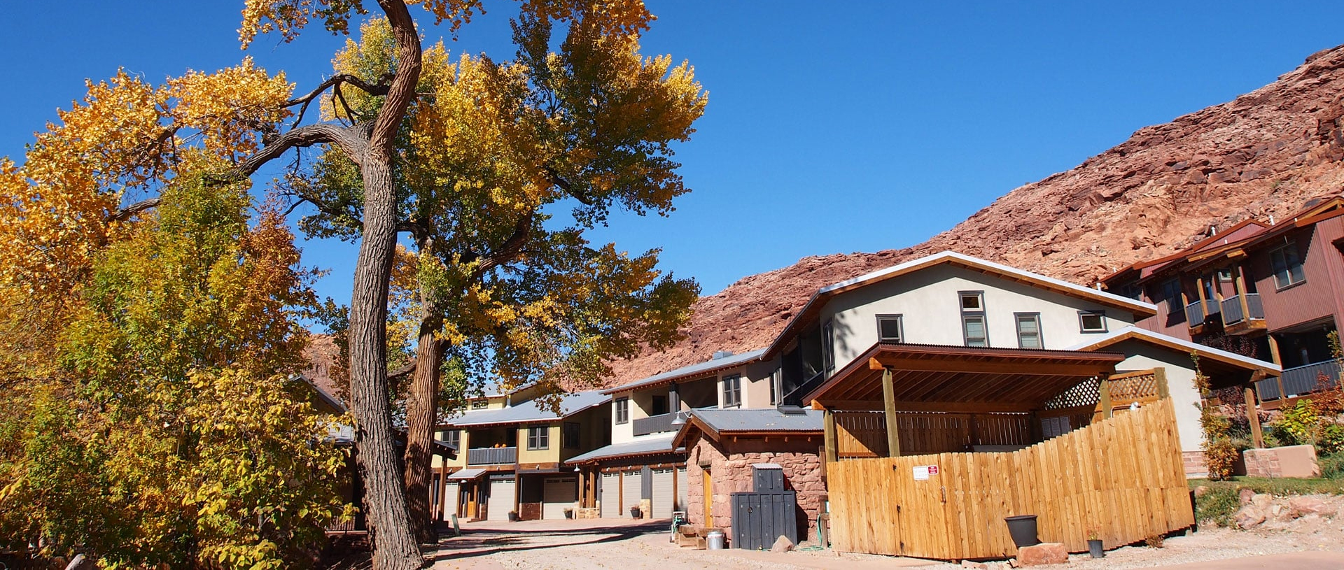 Tall majestic trees bearing orange and yellow leaves tower above triangular shaped roofs of townhomes at Moab Springs Ranch under bright blue skies.