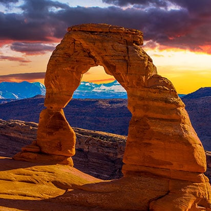 An arch structure of sandstone stands against the background of La Sal Mountains in the glow of sunset at Arches National Park in Utah.
