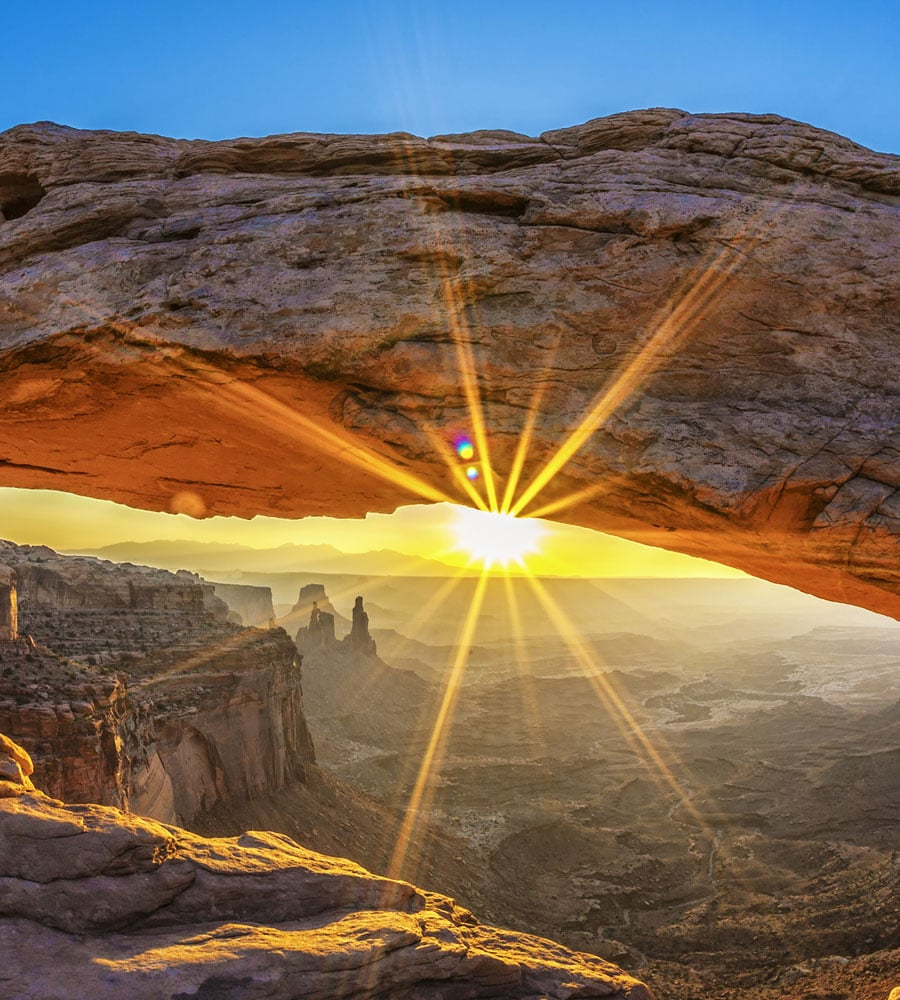 A partial view of the underside of a sandstone arch overlooking the vast hills and valleys of Arches National Park in Moab, Utah.