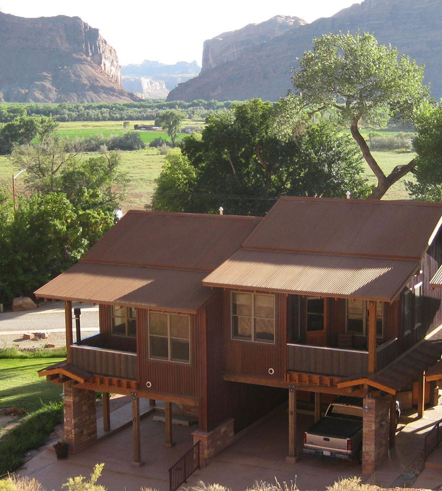 A view of two attached bungalow Units on Moab Springs Ranch, each with a two-car garage, standing amongst tall green trees and towering cliffs in the background.