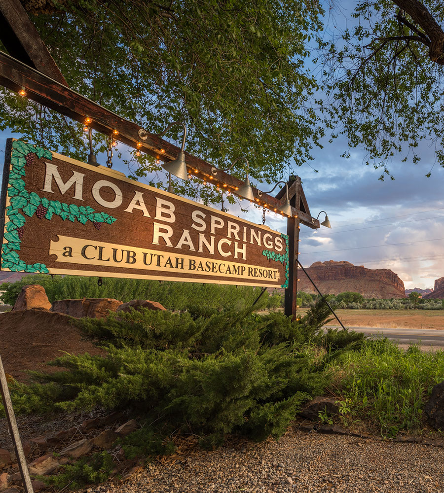The Moab Springs Ranch corporate logo is a large wooden rectangular sign placed by the roadside illuminated by sign lamps for arriving guests.