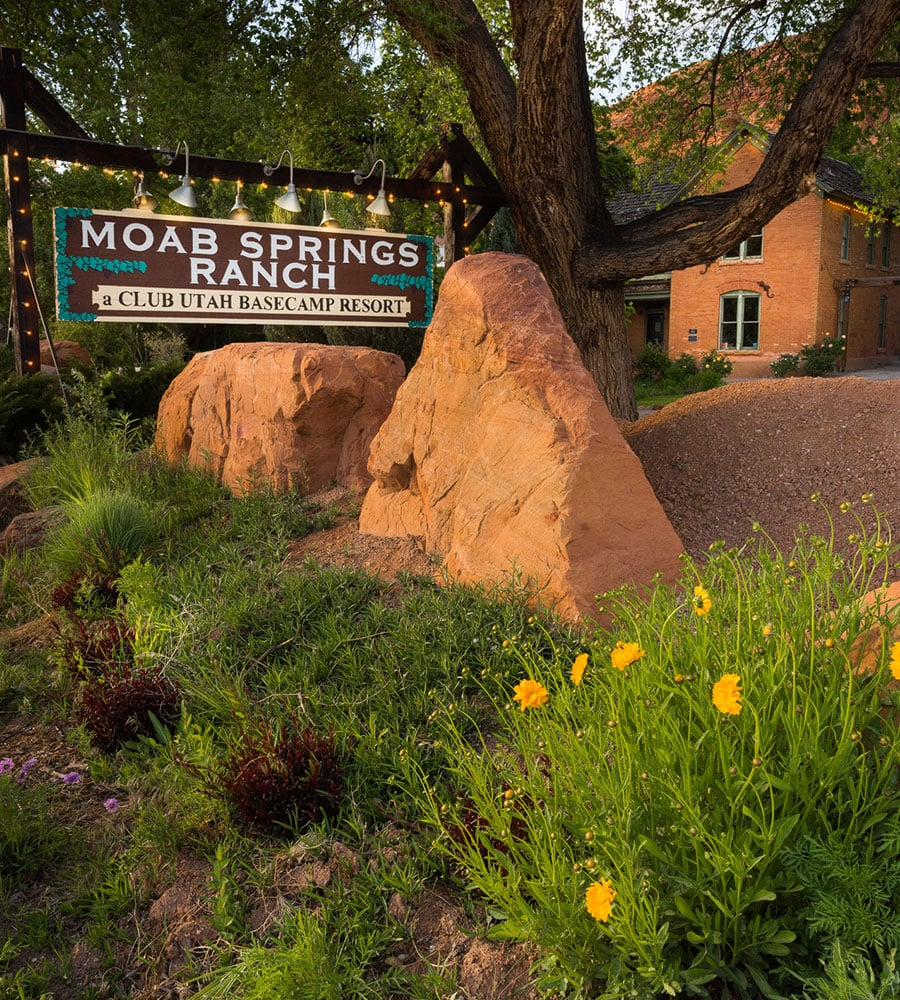 The Moab Springs Ranch roadside sign is placed amongst large boulders and a tall cottonwood tree in front of the faded red brick National Historic Register Ranch House.