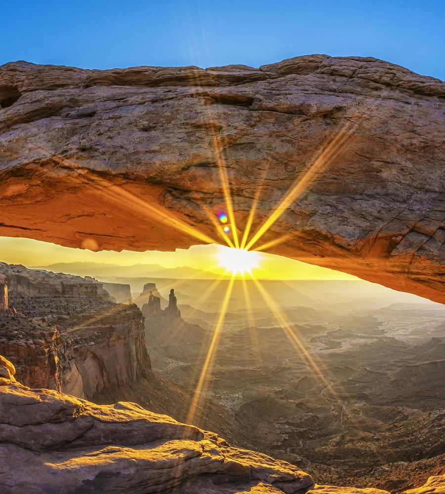 A view of a sandstone arch overlooking the bright sun and vast valley of sandstone cliffs at Arches National Park in Utah.