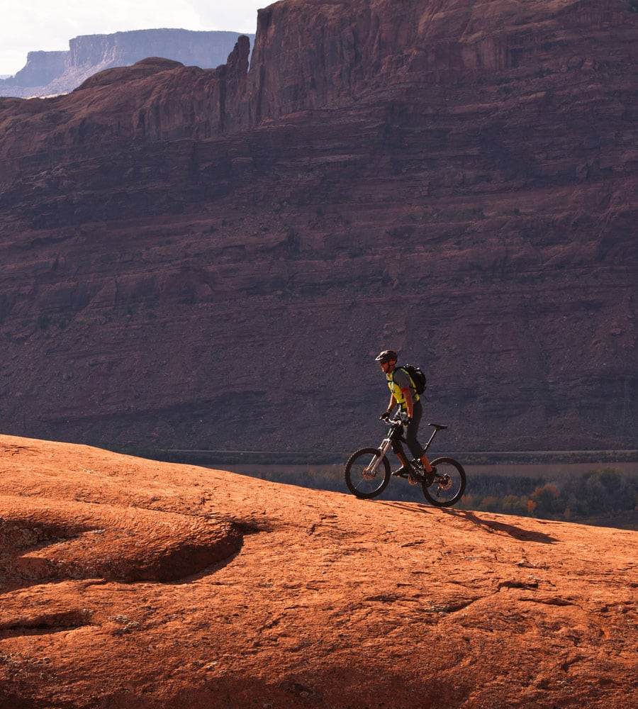 A male mountain biker is riding up a biking trail against the backdrop of a towering sandstone cliff in Moab, Utah.