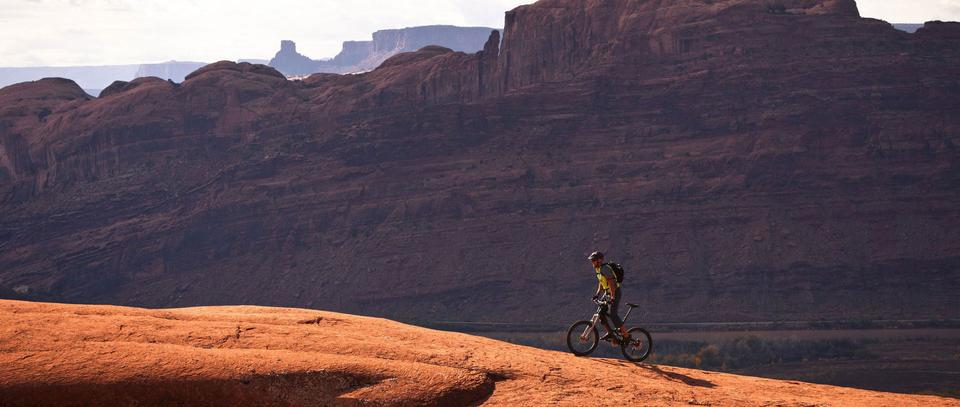 A large panoramic view of the monolithic mountains and sandcliffs of Moab, Utah and a lone male mountain biker riding up a trail.