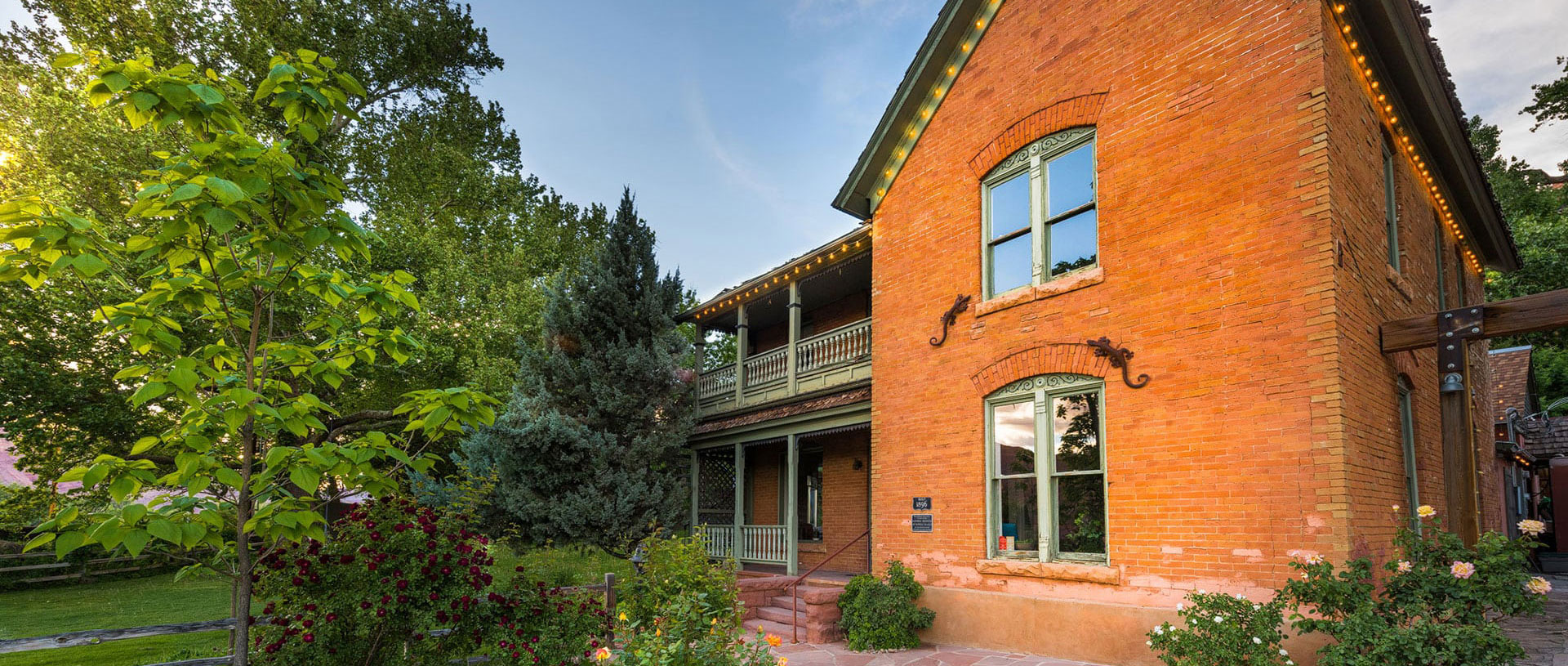 The historic ranch house on the Moab Springs property is a two storey faded red brick structure with a covered balcony on the upper floor overlooking lush vegetation.