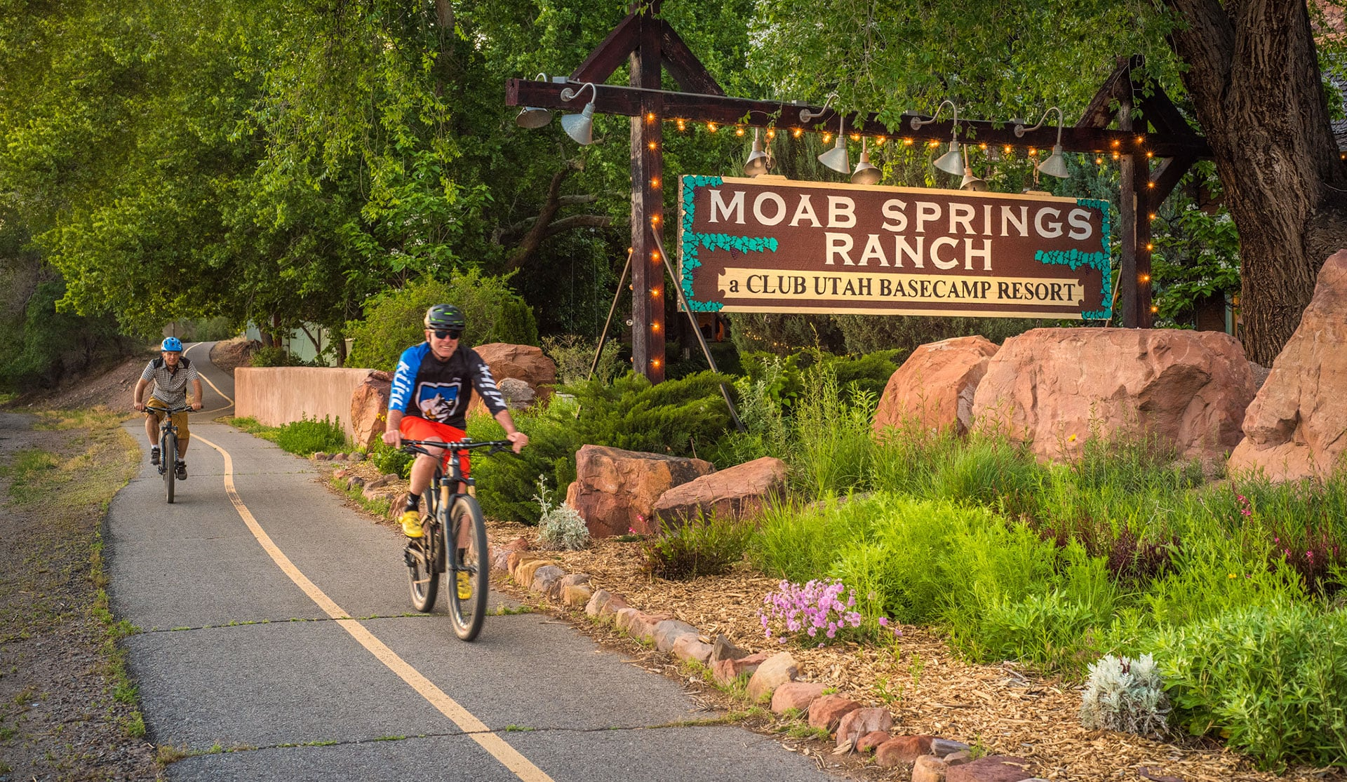 Two male bicyclists ride past canopies of green leaves from tall cottonwood trees, multi colored flora, large sandstone boulders and the rectangular Moab Springs Ranch sign.