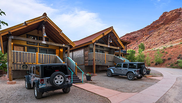 A bungalow unit made entirely of brown wood slats features large woodframed windows, a spacious porch and a sturdy staircase at Moab Springs Ranch.
