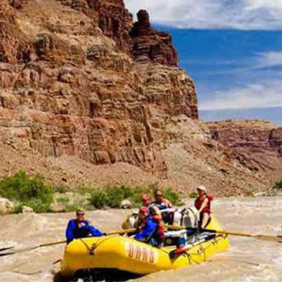 A small photograph of adventurers on a yellow inflatable raft, riding the rapids of the Colorado River with towering rusty brown sandcliffs in the background.