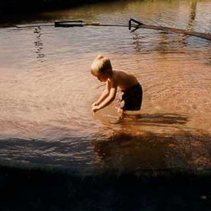 A shirtless blonde male child, dressed in dark shorts plays in a freshwater pond at Moab Springs Ranch.