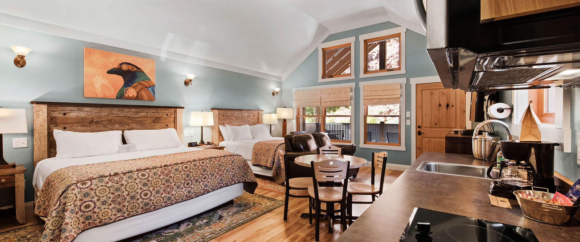The bedroom of Unit #19 at Moab Springs Ranch is furnished with a king sized bed with a circular geometric print cover, a solid brown wood headboard and white bedside tables.