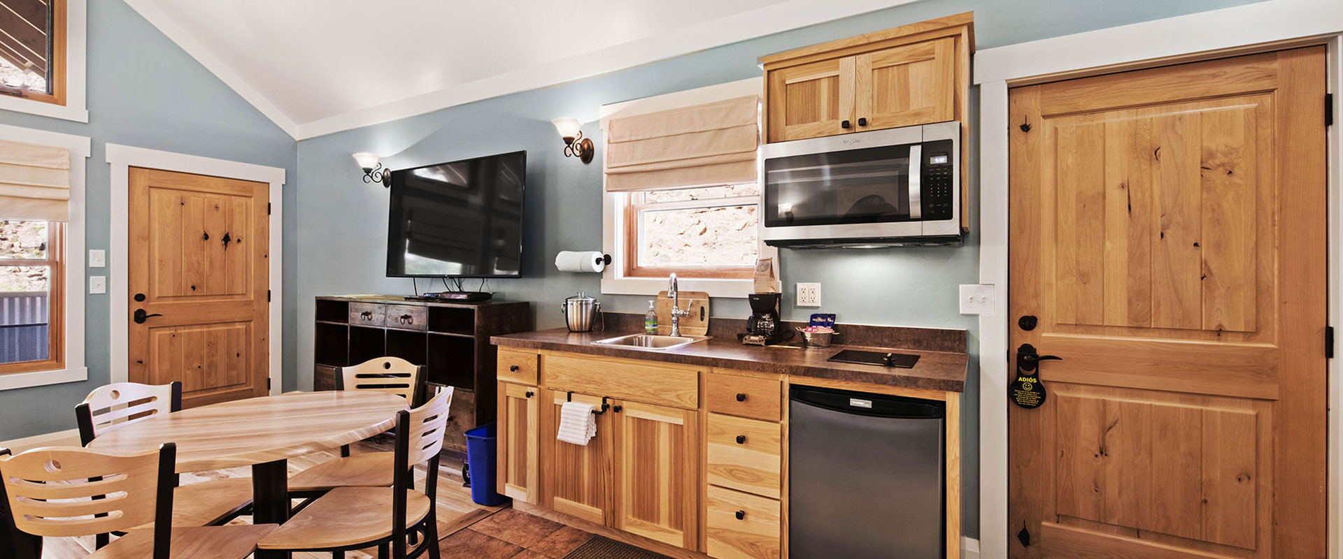 The fully equipped kitchen at Unit #18 at Moab Springs Ranch features honey wood color cupboards, gas stove, brown tile backsplash and countertops, and a wrap around island.