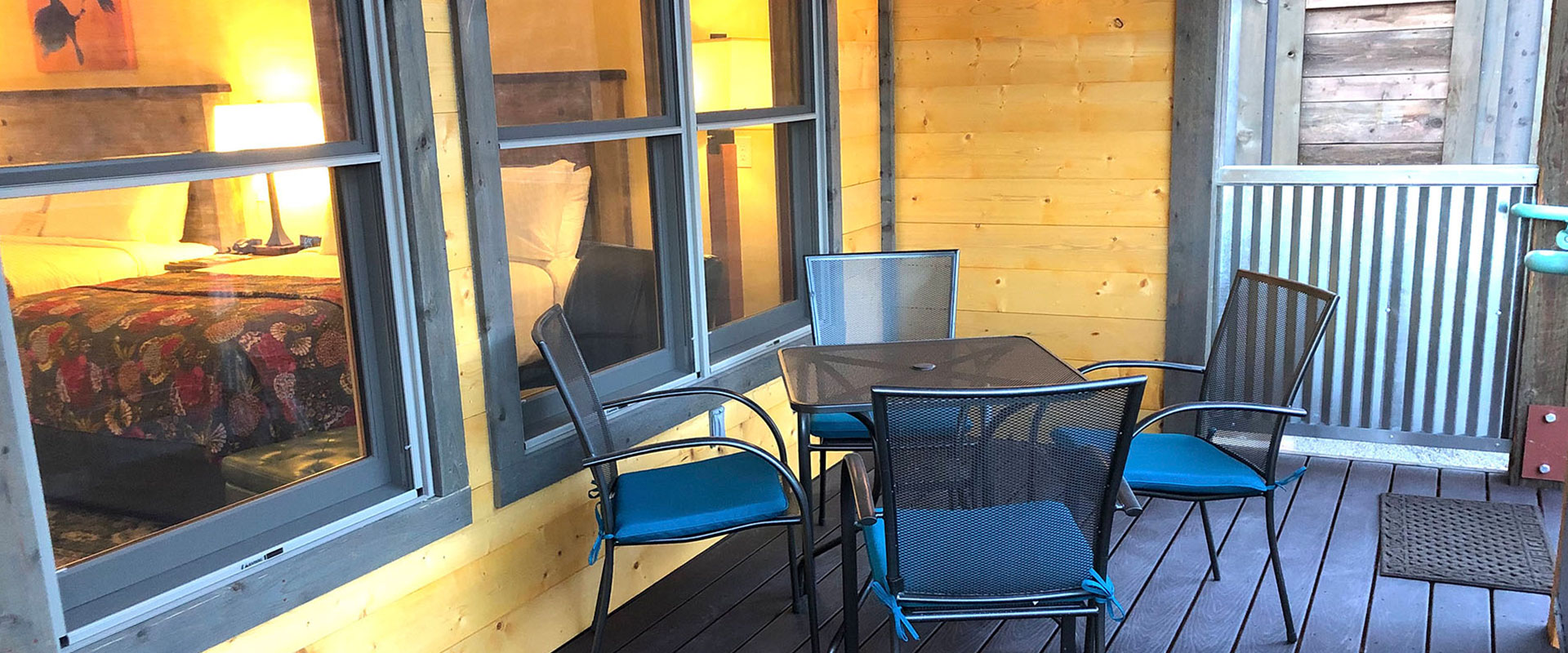 The outdoor space of a housing unit on Moab Springs Ranch has sturdy metal chairs and table, a black woodburning fireplace, barbecue and corrugated metal enclosure.