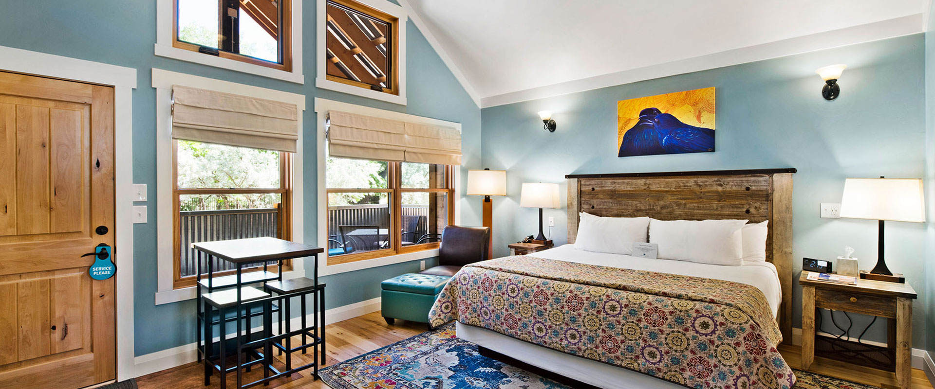 A panoramic view of the fully equipped kitchen in Unit #21 at Moab Springs Ranch with stainless steel appliances, a wrap around island that serves as a breakfast bar and flatscreen TV.