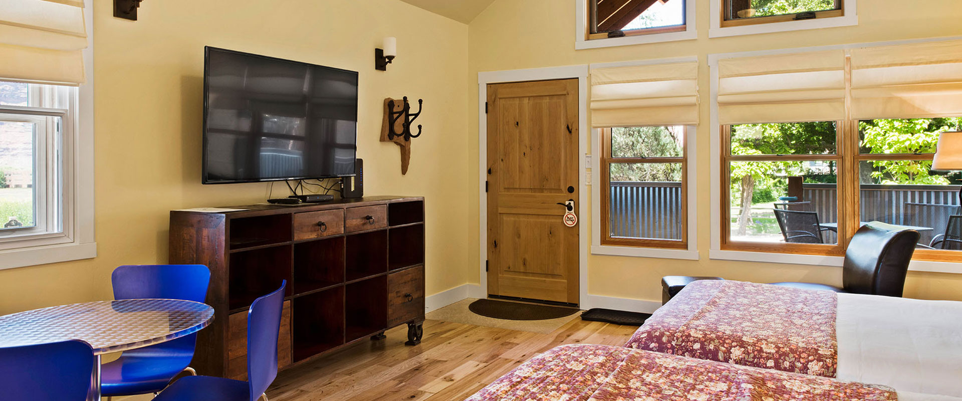 A black wood framed queen sized bed, covered in a multi-colored geographical print is presented with three large white pillows at a bedroom suite in Unit #21 at Moab Springs Ranch.