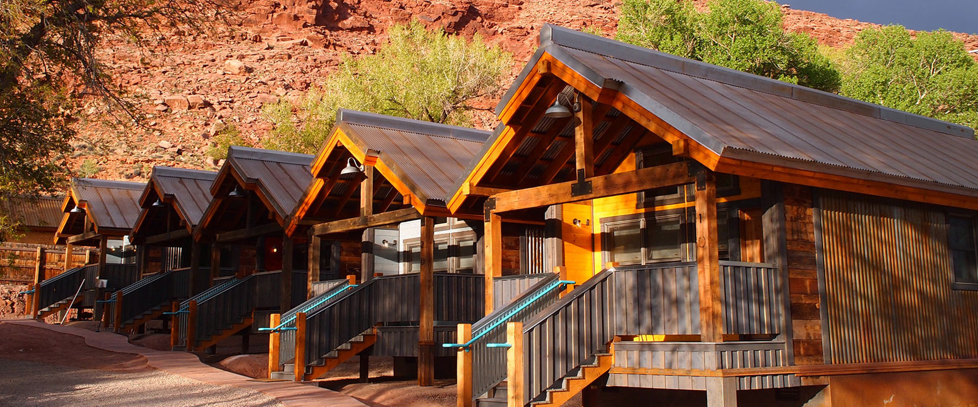 Upward looking view of trees bearing green and yellow leaves towering over the townhomes of Moab Springs Ranch.