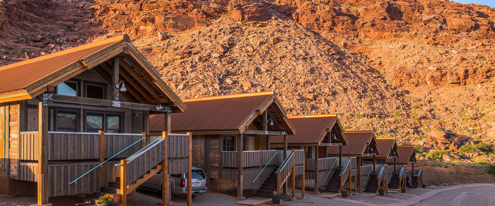Rows of triangular rooftops of townhouses at Moab Springs Ranch are set against the background of sandcliffs, pale green grasslands and tall lush cottonwood trees.