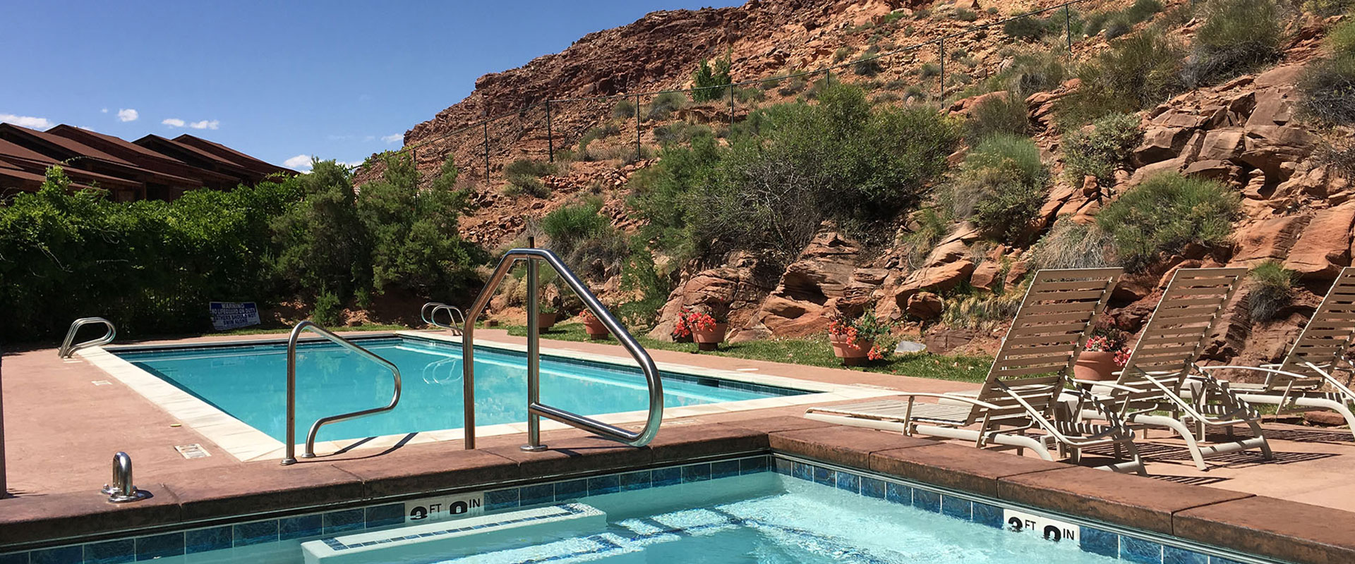 The Moab Springs Ranch road sign, illuminated by silver gooseneck lamps, is placed amongst a towering tree, weather-worn boulders and green vegetation.