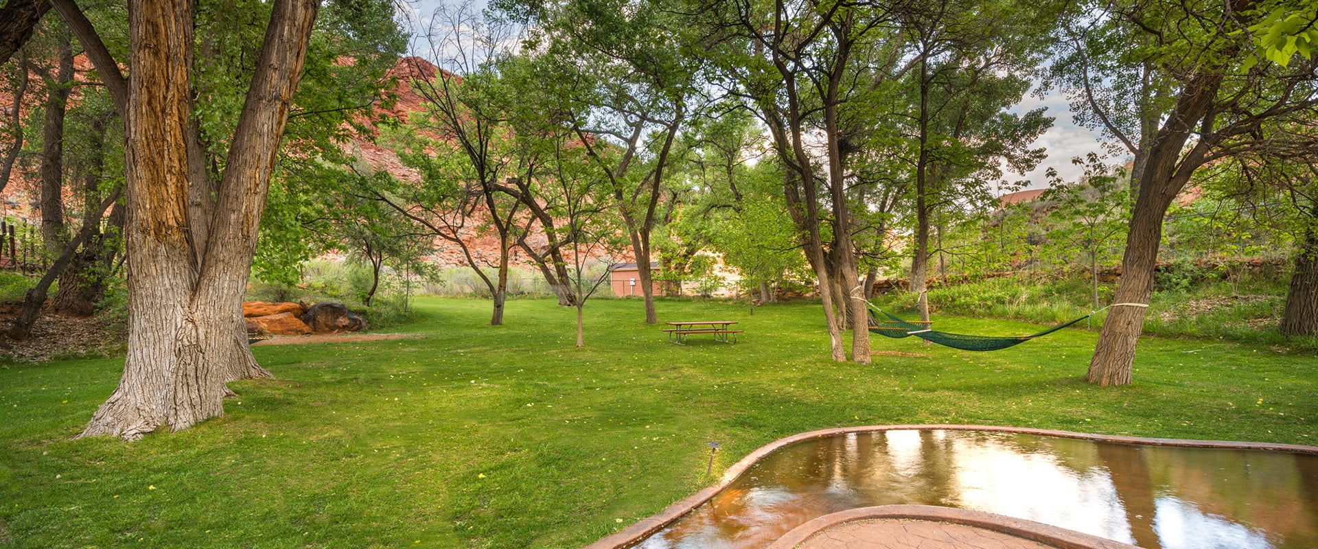 A man-made stream runs across the parkspace of Moab Springs Ranch with towering green trees, a hammock and a picnic table in the background.