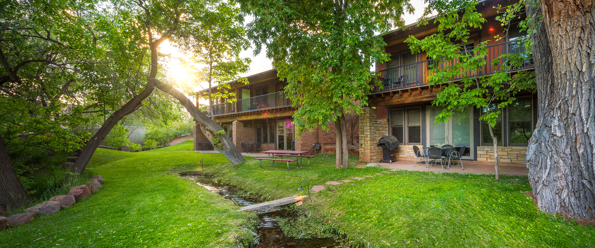 A man-made stream runs by lounge chairs, picnic tables, hammocks and tall cottonwood trees in the green parkspace at Moab Springs Ranch in Utah.