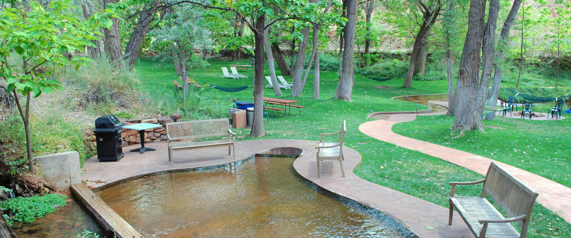 Clusters of purple wisteria hang over a steel rod fence enclosing a lounge area with a chaise lounge, patio seats, and filigree ironwork tables at Moab Springs Ranch.
